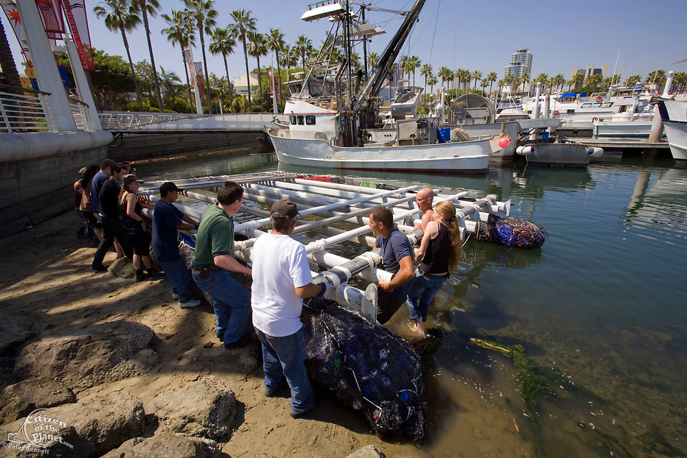 """Volunteers help with Initial test launch of Junk raft.  in the Summer of 2008, the raft called """"Junk""""  will sail 2,100 miles from Los Angeles through the North Pacific Gyre, on raft made of junk. Designed by Dr. Marcus Eriksen and Joel Paschal, the raft, dubbed """"Junk"""" will be constructed from 20,000 plastic bottles, an airplane fuselage, discarded fishing nets, a solar generator, and a bicycle generator. Long Beach, California, USA"""