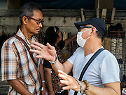 27 NOVEMBER 2015 - BANGKOK, THAILAND: A man talks an amulet vendor in front of the vendor's stall on Maharat Road in Bangkok. Hundreds of vendors sell amulet and Buddhist religious paraphernalia to people in the Amulet Market, a popular tourist attraction along Maharat Road north of the Grand Palace near Wat Maharat in Bangkok. Bangkok municipal officials announced that they are closing the market and forcing vendors to relocate to an area about one hour outside of Bangkok. The closing of the amulet market is the latest in a series of municipal efforts to close and evict street vendors and markets from areas that have potential for redevelopment. The street vendors will be evicted from the area by Sunday, Nov. 29.    PHOTO BY JACK KURTZ