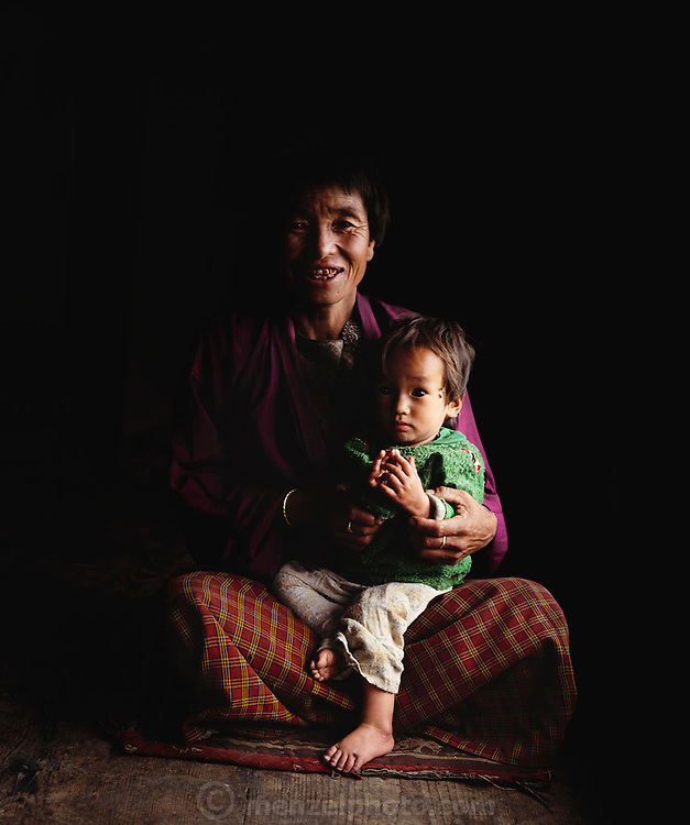 Family matriarch Nalim with her youngest daughter Zekom. Nalim's teeth are damaged by the use of betel nut (a mildly narcotic tree fruit). Shingkhey Village, Bhutan. From Peter Menzel's Material World Project.