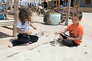 Israel, Tel Aviv, a seaside cafe and restaurant Two children (boy and girl) play in the sand