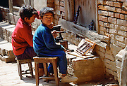 Young child workers painting carvings, Bhaktapur, Nepal