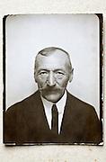 vintage passport style photo of elderly man with mustache