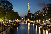 Westerkerk church and canal barges from Prinsengracht in Amsterdam, Holland