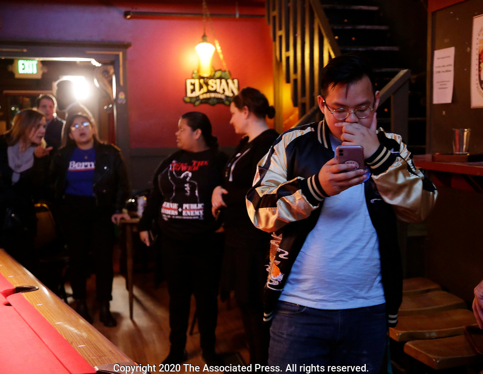 Rico Doan, right, checks the first results of Washington state primary results on his phone at an informal campaign party for Democratic presidential candidate Sen. Bernie Sanders, I-Vt. as the first results come in for the Washington State primary, Tuesday, March 10, 2020, in Seattle. (AP Photo/John Froschauer)