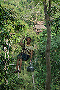 LAOS, Bokeo Nature Reserve, tropical rainforest, Gibbon Experience: ecotourism and conservation project, woman, cooking on zip line with tea pot
