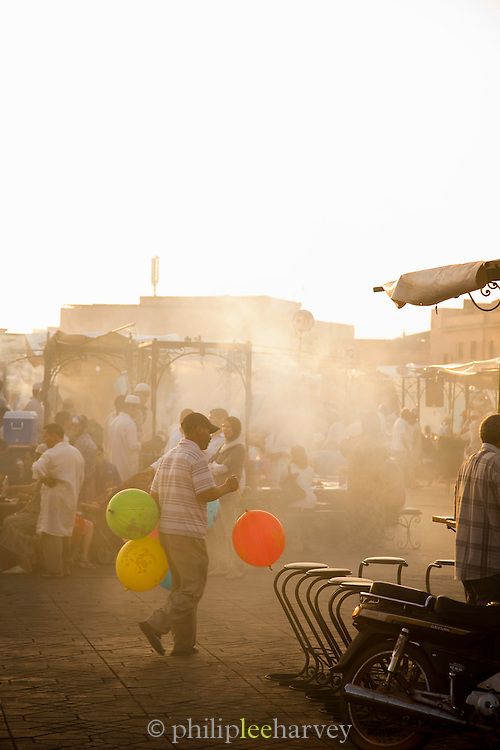 A man selling balloons among the food stalls in the Djemaa el Fna in the medina of Marrakech, Morocco