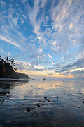 Evening light reflects in the flat sand of Ruby Beach along the Pacific Ocean on Washington's Olympic Peninsula in Olympic National Park.