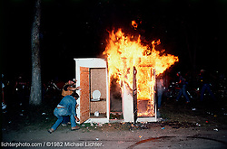 Up in Flames, Sturgis, South Dakota, 1982<br /> <br /> Limited Edition Print from an edition of 50. Photo ©1982 Michael Lichter.<br /> <br /> The Story:This is what ended it for City Park. The campers were so fed up with the Porta-lets not being emptied and overflowing that they took matters into their own hands. The years of camping and the parties were over. By 1983, it was chained and locked forever.