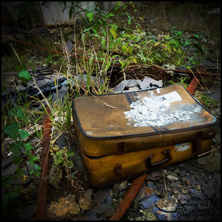Abandoned suitcase in a room without a roof