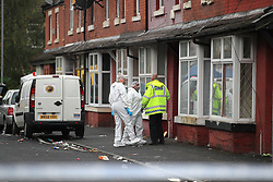 Police speak with forensics officers at the scene in Claremont Road, Moss Side, Manchester, where several people have been injured after a shooting.