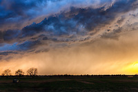 The sun sets behind an approaching thunderstorm in Oklahoma