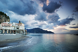 Stormy Sky, sunrise, Atrani Italy. Stretching about 30 miles or 50km along the southern side of the Sorrentine Peninsula, most famous for the town of Sorrento, the Amalfi Coast (Costiera Amalfitana) is one of Europe's most breathtaking. Cliffs terraced with scented lemon groves sheer down into sparkling seas; whitewashed and pastel colored villas cling precariously to unforgiving slopes while sea and sky merge in one vast blue horizon.