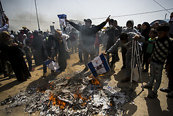 April 13, 2018 - Gaza City, The Gaza Strip, Palestine - Palestinian protesters set fire to an Israeli flag during clashes with Israeli security forces along the borders between Israel and Gaza Strip, east of Gaza City in the central Gaza Strip on April 13, 2018. Palestinians are marching for the 3rd week of a six-week long protest, along the Gaza-Israel border, to highlight the hundreds of thousands of Palestinian refugees who were expelled or fled their homes during the 1948 war that marked Israel's creation. (Credit Image: © Mahmoud Issa/Quds Net News via ZUMA Wire)
