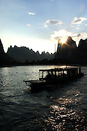 Sunset on the river Li in Yangshuo with a tourist barge sailing