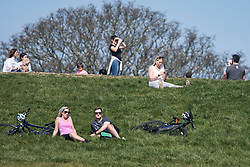 © Licensed to London News Pictures. 10/04/2020. London, UK. People sunbathing on Primrose Hill in London as police cycled past, during a pandemic outbreak of the Coronavirus COVID-19 disease. The public have been told they can only leave their homes when absolutely essential, in an attempt to fight the spread of coronavirus COVID-19 disease. Photo credit: Ben Cawthra/LNP