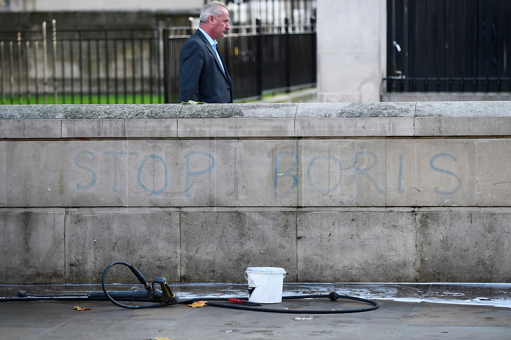 © Licensed to London News Pictures. 22/10/2019. LONDON, UK.  A workman's hose and bucket next to a wall in Whitehall opposite Downing Street which shows the graffiti STOP BORIS, which is in the process of being cleaned off.  MPs are due to vote in the House of Commons on whether to support the Prime Minister's European Union (Withdrawal Agreement) Bill.  If approved, MPs will then be asked to support a three-day schedule in which to consider the relevant legislation, but critics have said that it is not enough time to analyze the 110 page document in detail.  Photo credit: Stephen Chung/LNP
