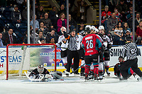 KELOWNA, CANADA - MARCH 16: David Tendeck #30 of the Vancouver Giants makes a save as referee Mark Pearce tries to restore order between players against the Kelowna Rockets  on March 16, 2019 at Prospera Place in Kelowna, British Columbia, Canada.  (Photo by Marissa Baecker/Shoot the Breeze)