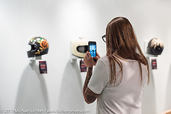 Christina Platis takes a photo of the helmet she painted for the Old Iron - Young Blood exhibition during the media and industry reception in the Motorcycles as Art gallery at the Buffalo Chip during the annual Sturgis Black Hills Motorcycle Rally. Sturgis, SD. USA. Sunday August 6, 2017. Photography ©2017 Michael Lichter.