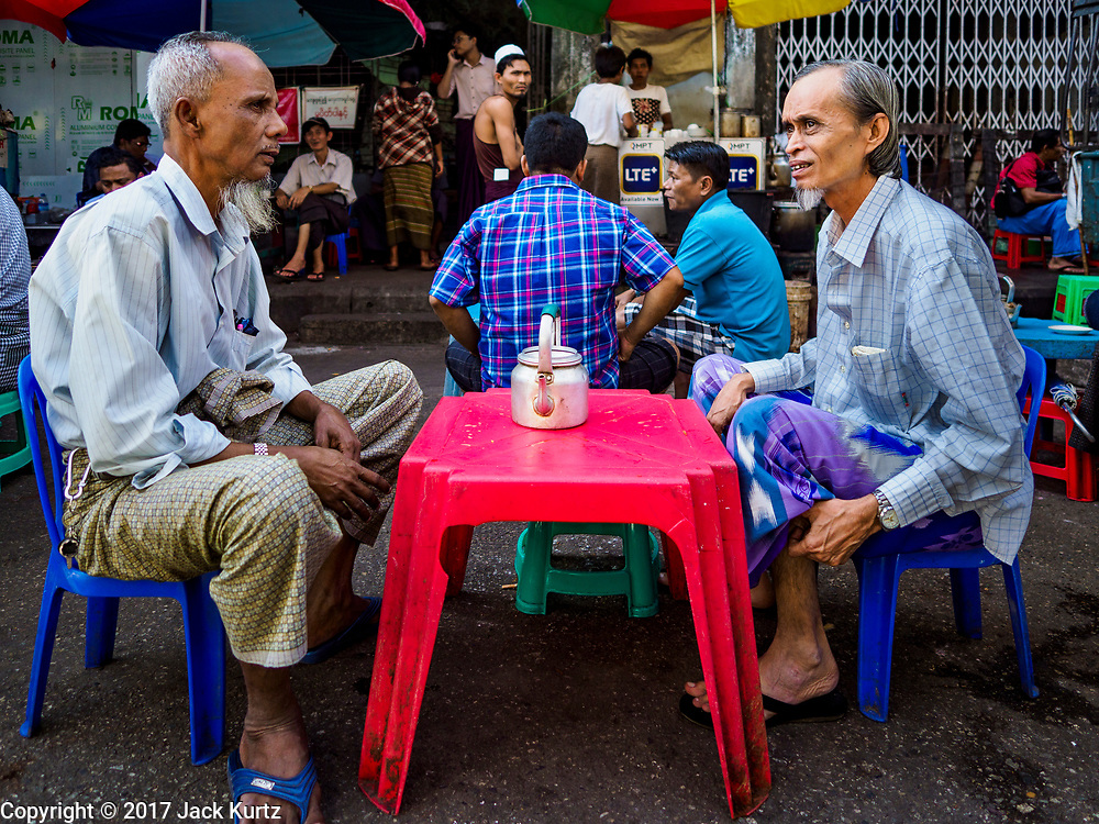 """24 NOVEMBER 2017 - YANGON, MYANMAR: Muslim men in Yangon have tea at a tea stand after Friday midday prayers. Many Muslims in overwhelmingly Buddhist Myanmar feel their religion is threatened by a series of laws that target non-Buddhists. Under the so called """"Race and Religion Protection Laws,"""" people aren't allowed to convert from Buddhism to another religion without permission from authorities, Buddhist women aren't allowed to marry non-Buddhist men without permission from the community and polygamy is outlawed. Pope Francis is to arrive in Myanmar next week and is expected to address the persecution of the Rohingya, a Muslim ethnic minority in western Myanmar. Some Muslims and Christians are concerned that if the Pope's comments take too strong of pro-Rohingya stance, he could exacerbate religious tensions in the country.  PHOTO BY JACK KURTZ"""