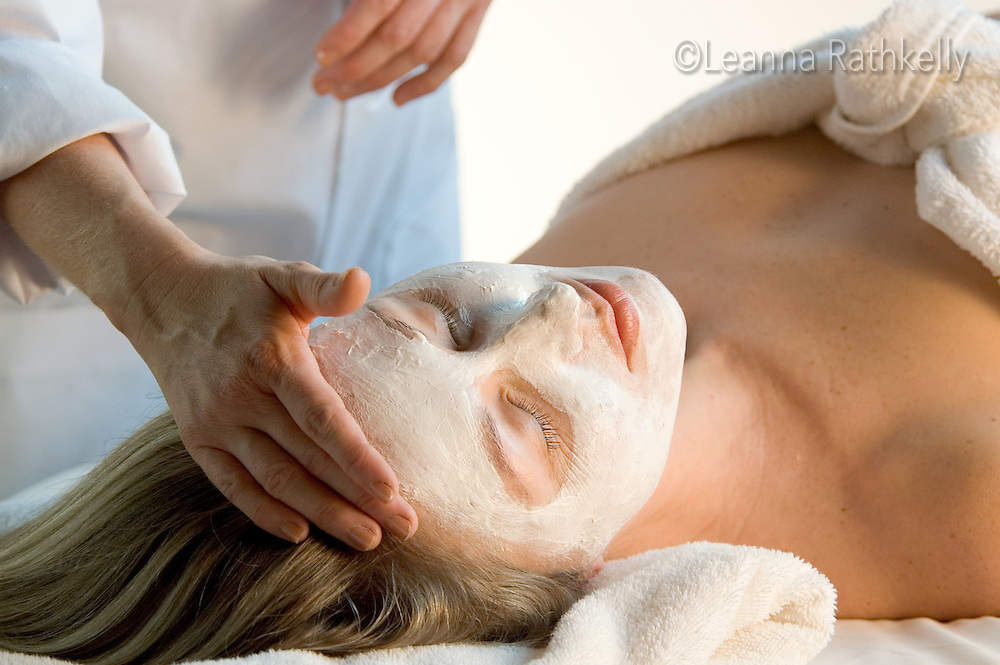 Woman gets facial, white mask