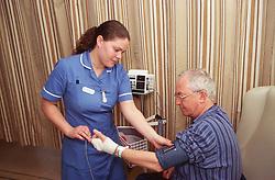 Female nurse taking elderly man's blood pressure,