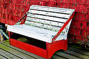 An empty white bench sits next to a lobster shack in Maine.