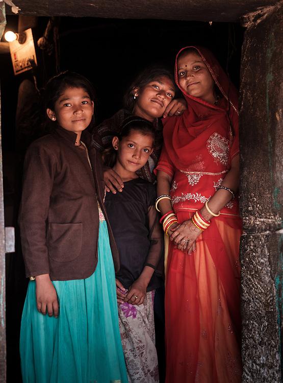 DECHU, INDIA - CIRCA NOVEMBER 2018: Family at their doorway on village in Dechu, Rajasthan.