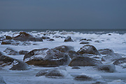 Ice and snow covers stones on the rocky beach on cloudy and grey day, Kaltene Seacoast, Kurzeme, Latvia Ⓒ Davis Ulands | davisulands.com