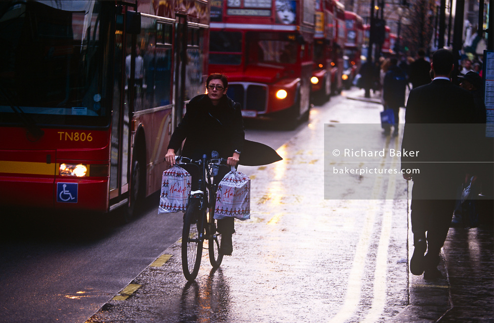 A nineties lady with Harrods shopping bags on each handlebar rides her bicycle past a line of red London buses, on 18th December 1999, in Oxford street, in London, England.