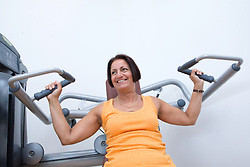 Woman using the chest press at her sports leisure centre,