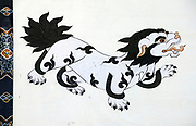 Representation the mythical Snow Lion painted in traditional Bhutanese style on the wall of a house.  The snow lion is a white dog-like creature with a black mane, tail and markings.  Paro,  Druk Yul, Kingdom of Bhutan. 10 November 2007.