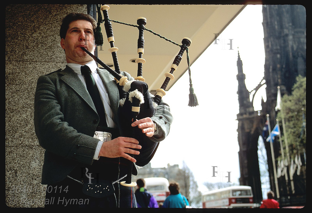 Bagpiper plays for small change from passers-by on Princes Street in downtown Edinburgh. Scotland