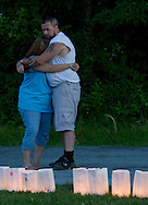 Pine Bush, New York - People from the Pine Bush community hug during the luminaria ceremony in the Relay for Life on Saturday, June 7, 2014. The Relay for Life is the American Cancer Society's largest fundraising event. ©Tom Bushey / The Image Works