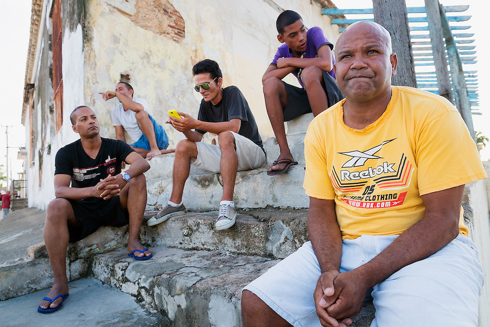 A group of residents sit together on a corner in the city of Mariel, Cuba across the Mariel Bay from a new Special Development Zone of Mariel on July 9, 2015. (David Albers/Staff)