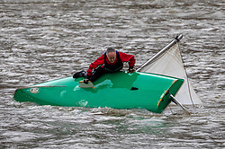 © Licensed to London News Pictures. 15/02/2020. London, UK. A dingy capsizes on the river Thames at Putney during Storm Dennis. The sailor scrambles for the safety of the hull before righting it. Unfortunately it seems to have broken its mast as Storm Dennis hits London and the South East with high winds and heavy rain forecast for the weekend. Photo credit: Alex Lentati/LNP