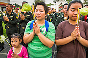 "25 FEBRUARY 2013 - BANGKOK, THAILAND:   A Thai family prays in front of Wat Benchamabophit Dusitvanaram (popularly known as either Wat Bencha or the Marble Temple) on Makha Bucha Day. Makha Bucha is a Buddhist holiday celebrated in Myanmar (Burma), Thailand, Cambodia and Laos on the full moon day of the third lunar month (February 25 in 2013). The third lunar month is known in Thai is Makha. Bucha is a Thai word meaning ""to venerate"" or ""to honor"". Makha Bucha Day is for the veneration of Buddha and his teachings on the full moon day of the third lunar month. Makha Bucha Day marks the day that 1,250 Arahata spontaneously came to see the Buddha. The Buddha in turn laid down the principles his teachings. In Thailand, this teaching has been dubbed the 'Heart of Buddhism'.    PHOTO BY JACK KURTZ"