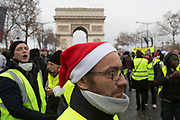 December, 8th, 2018 - Paris, Ile-de-France, France: Protester with Father Christmas hat with Arc de Triomphe behind on Champs Elysees. The French 'Gilets Jaunes' demonstrate a fourth day. Their movement was born against French President Macron's high fuel increases. They have been joined en mass by students and trade unionists unhappy with Macron's policies. Nigel Dickinson