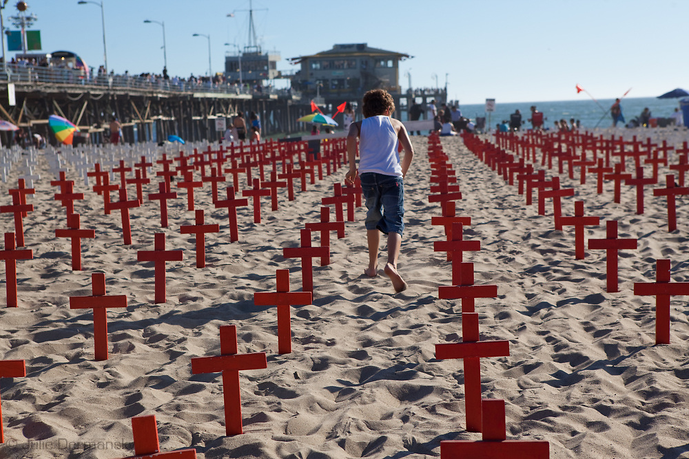 Kid playing amongst a field of red crosses at Arlington West in Santa Monica