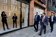 As businessmen walk past, staff at the Gagosian Art Gallery in Davies Street, Mayfair London stand in the window with a kneeling Hitler called La Fine di Dio by Maurizio Cattelan. The controversial artwork is featured in this Mayfair gallery window and the employees stand prominently to avoid trouble.