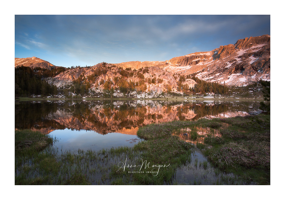 Evening light illuminating the background to Lower Young lake and reflecting it in the water, Yosemite Backcountry, California