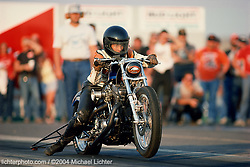 Lori Dalton Off the Line. Sturgis, SD. 1988<br /> <br /> Limited Edition Print from an edition of 50. Photo ©1988 Michael Lichter.<br /> <br /> The Story: I was impressed.  There was something about the way Lori sat so nimbly on her 500 pound Harley-Davidson, feet barely touching the ground with eyes peering ahead awaiting the green light.  With the crack of her wrist, she lifted the front end off the ground and drove the power to the back tire, twisting and contorting it as it gripped the asphalt to propel her down the strip.