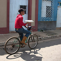Central America, Cuba, Remedios. Boy delivers eggs on his bicycle in Remedios.