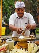 16 JULY 2016 - UBUD, BALI, INDONESIA: A Hindu priest prepares an alter before the mass cremation in Ubud Saturday. Local people in Ubud exhumed the remains of family members and burned their remains in a mass cremation ceremony Wednesday. Almost 100 people were cremated and laid to rest in the largest mass cremation in Bali in years this week. Most of the people on Bali are Hindus. Traditional cremations in Bali are very expensive, so communities usually hold one mass cremation approximately every five years. The cremation in Ubud concluded Saturday, with a large community ceremony.     PHOTO BY JACK KURTZ