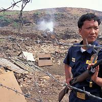 Philippines, Luzon Island, Panfilo Arranchado is armed guard at Manila's Smokey Mountain garbage dump