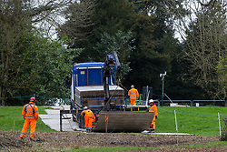 Denham, UK. 4 February, 2020. Engineers working on the HS2 high-speed rail link project prepare to unload a temporary roadway from a large truck. Planned works in the immediate vicinity are believed to include the felling of 200 trees and the construction of a roadway, Bailey bridge, compounds, fencing and a parking area.