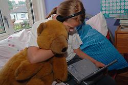 Girl watching DVD with headphones in her bedroom