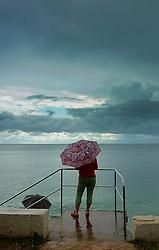24.07.2011, Porec, AUT, Feature, im Bild eine Frau mit Regenschirm steht an einem verregneten Urlaubstag sehnsüchtig am Meer, EXPA Pictures © 2012, PhotoCredit: EXPA/ Erwin Scheriau