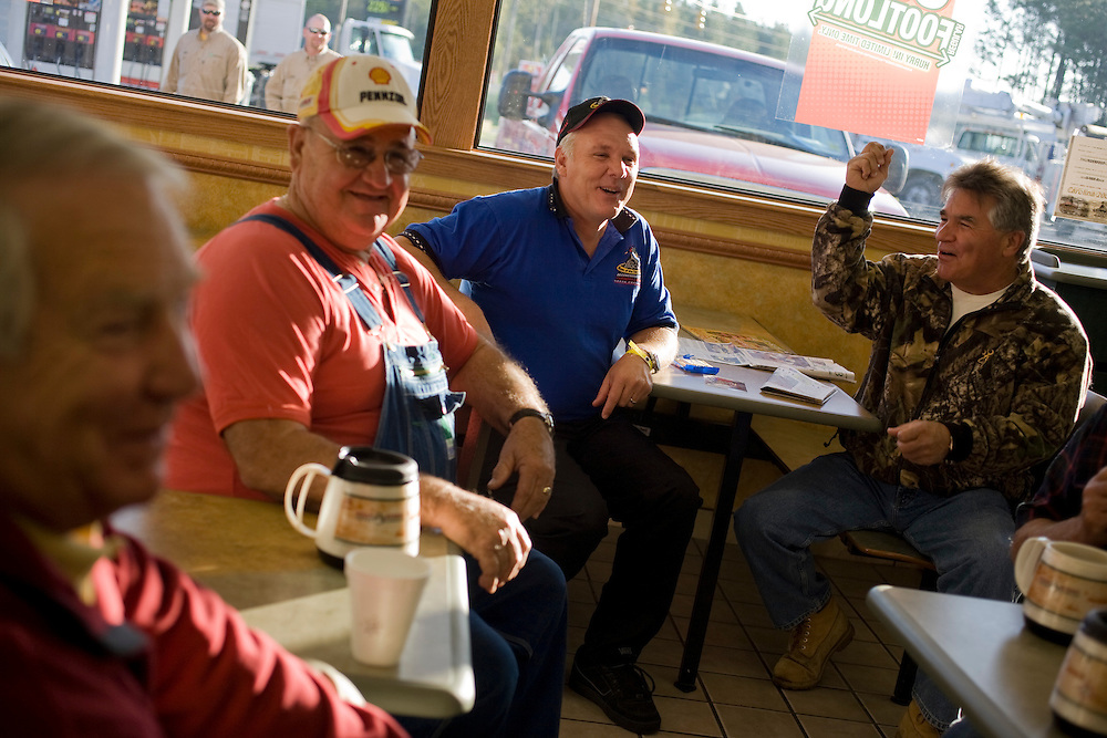 """On most weekday mornings Rockingham Speedway owner Andy Hillenburg, in blue polo, gathers with local friends at the Citgo gas station outside of Rockingham, N.C., to shoot the breeze. They call it """"The Barbershop."""" Pictured with Hillenburg are, from left, Bill Pattan and Bo Ussery."""