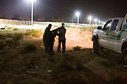 05 OCTOBER 2005 - DOUGLAS, AZ: US Border Patrols agents apprehend illegal immigrants from Mexico near Douglas, AZ. The lights and fence in the background are the US/Mexico border. Apprehensions of illegal immigrants in the Douglas area are down significantly in the last 18 months. In 2003, the Border Patrol apprehended an average of 1,500 people a day in and around Douglas. In September and October 2005 they are apprehending only about 150 - 200 people a day.  PHOTO BY JACK KURTZ