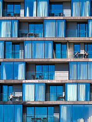 Close up of apartments, their owners and balconies near Butler's Wharf on the River Thames in London.